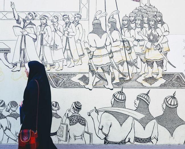 Woman walking in front of a wall in Tehran. Graffiti Soldiers Wall Wall Art Woman Abaya Adult Burka  Headscarf Hijab History Iran Islam Islamic Art Islamic Event Islamic History Muslim One Person Religion Religious  Side View Tehran War