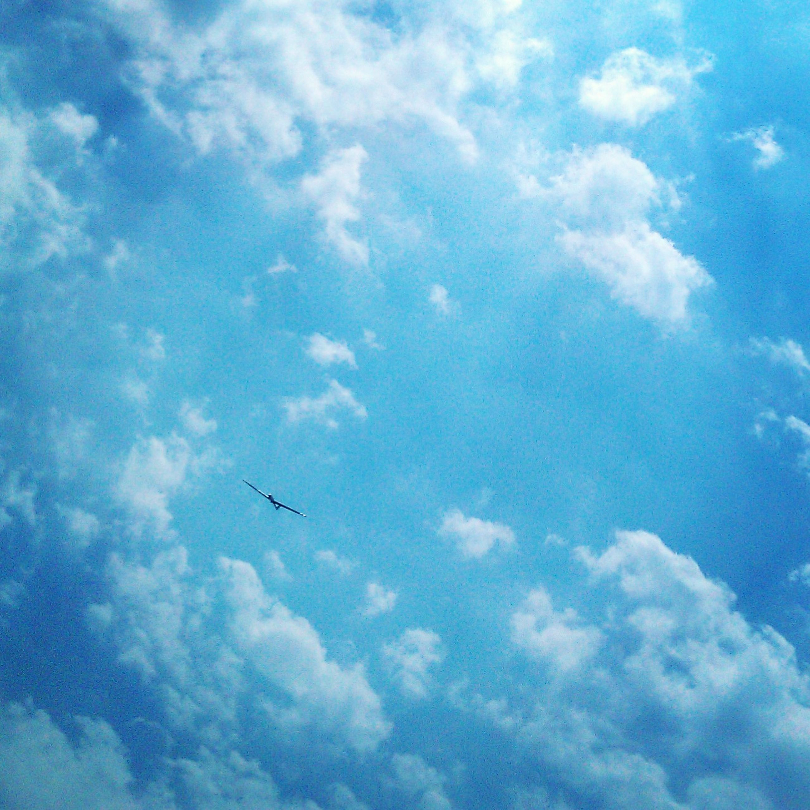 low angle view, sky, cloud - sky, blue, flying, transportation, airplane, air vehicle, mid-air, cloud, nature, mode of transport, cloudy, beauty in nature, sky only, tranquility, scenics, day, outdoors, cloudscape