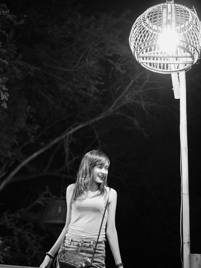Smiling woman standing by illuminated street light at night