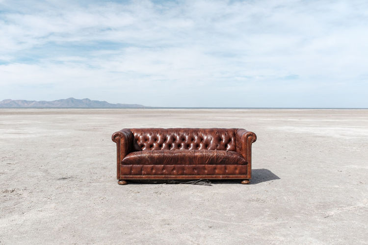 Sofa at salt flat against sky