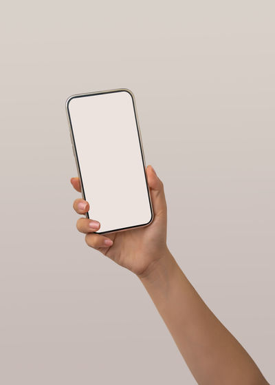 Low angle view of person using smart phone against white background