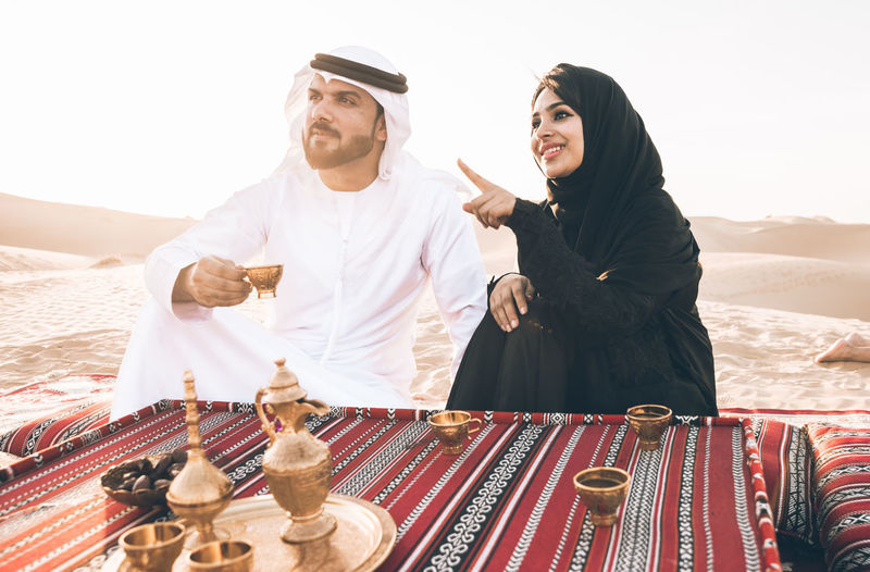 Smiling woman gesturing by man with tea sitting on carpet at desert