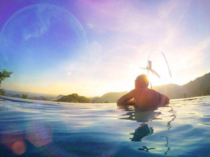 Rear view of man in infinity pool