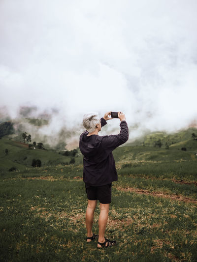 Rear view of person photographing on field