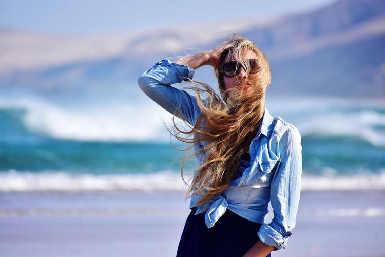 Mid adult woman with tousled hair standing at beach