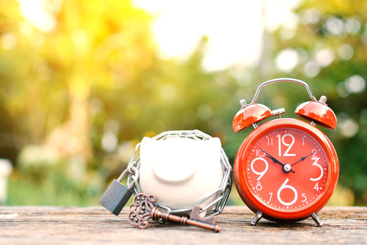 Close-up of red alarm clock with piggy bank on wooden table