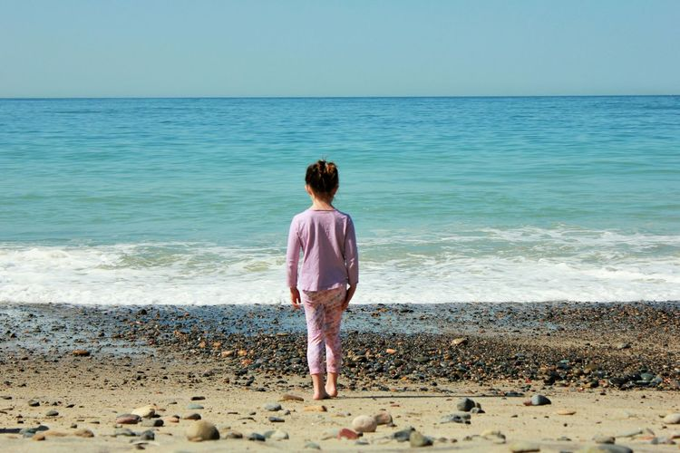 Rear View Of Girl Standing At Beach
