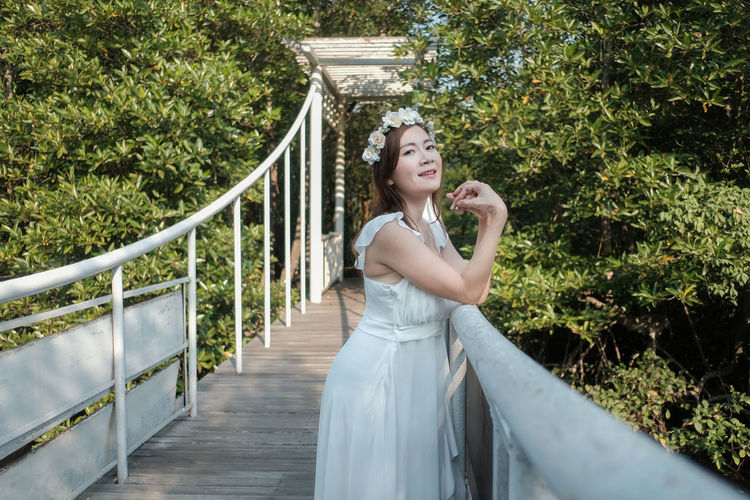 Portrait of bride standing by railing on footbridge in forest