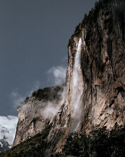 Low angle view of rock formation and waterfall against sky