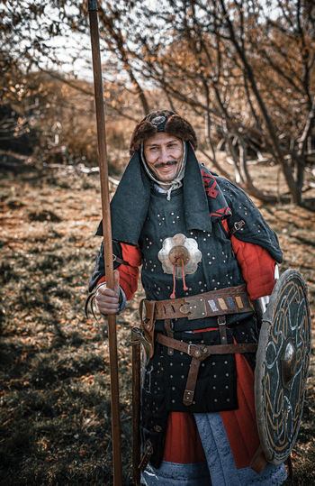 Portrait of smiling warrior standing in forest