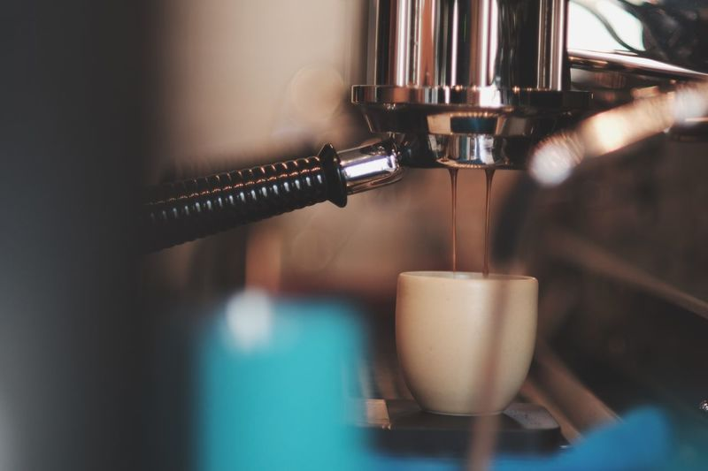 Close-Up Of Coffee Pouring In Cup From Machinery At Cafe