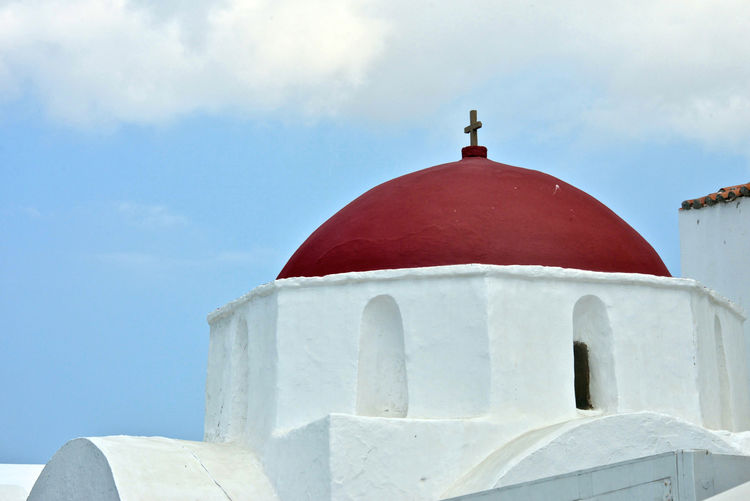 close up of a white greek church with red dome Sky Religion Belief Architecture Built Structure Place Of Worship Building Exterior Spirituality Dome Day No People Building Nature White Color Cross Whitewashed Outdoors Red Red Dome Greek Greek Church Detail Close Up Greek Architecture Mykonos,Greece