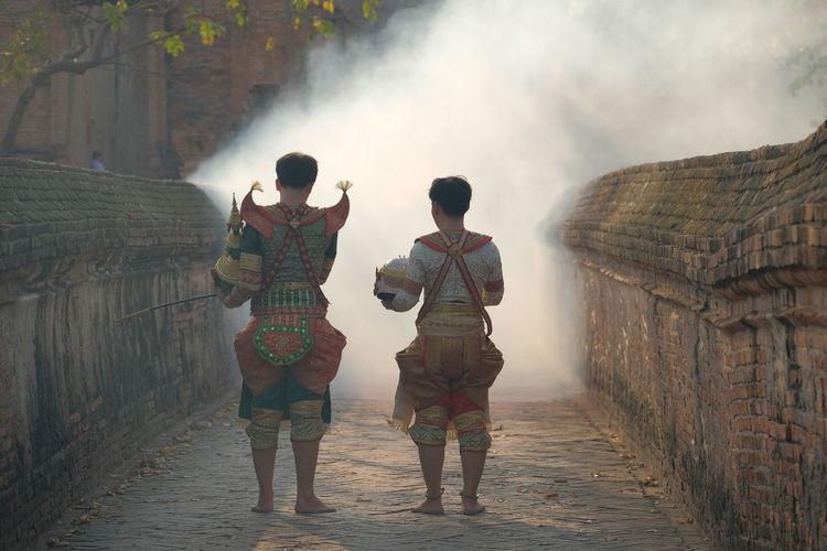 Rear view of people in costume walking on walkway