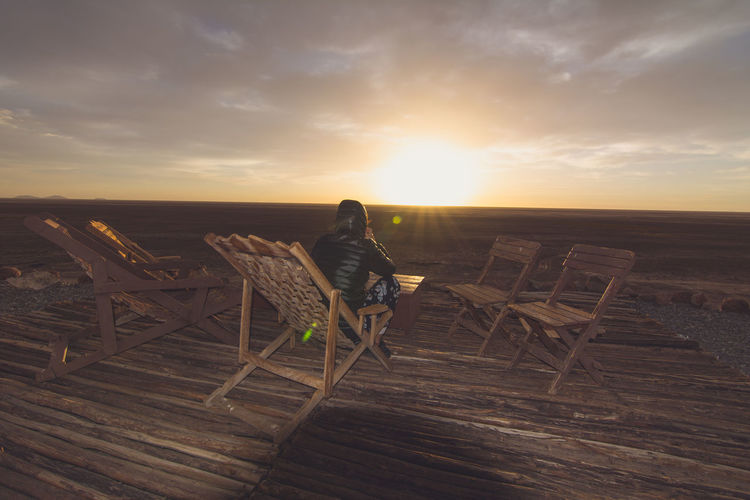 Rear View Of Person Sitting On Wooden Chair Against Sky At Sunset