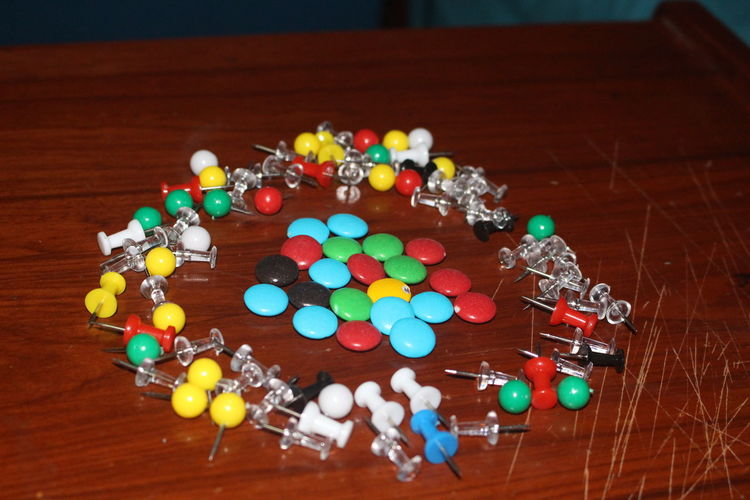 Colorful candies with thumbtacks on wooden table