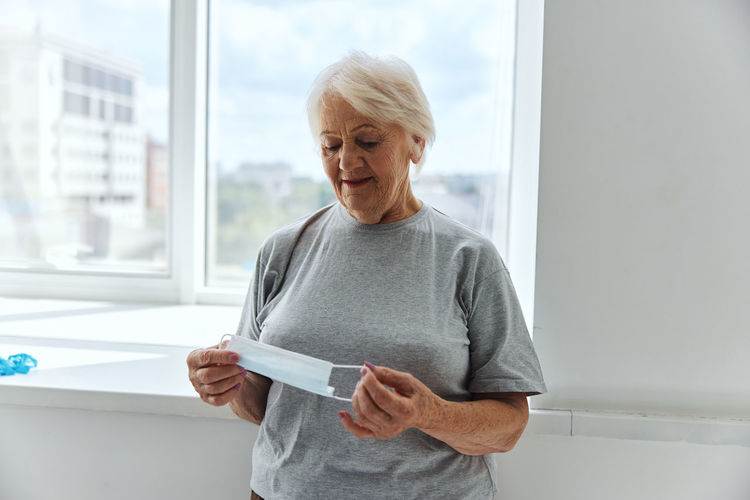 Mid adult woman standing against window