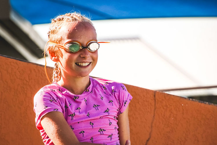 portrait of a young smiling girl wearing swimming goggles standing poolside in summertime Glasses Smiling Happiness Child Girls One Person Sunlight Emotion Day Sunglasses Portrait Eyeglasses  Casual Clothing Childhood Real People Lifestyles Leisure Activity Fashion Headshot Outdoors Purple Hairstyle Poolside Swimming Goggles