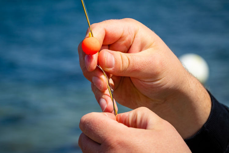 Close-up of hand holding fishing line