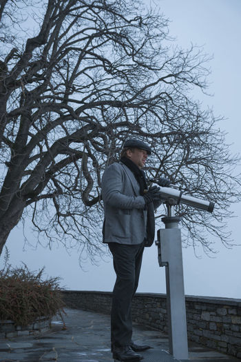 Elegant man and a Telescope Adults Only Bare Tree Branch Cold Temperature Day Flat Cap Fog Handsome Looking Down Men Nature One Man Only One Person Only Men Outdoors People Side View Sky Standing Suit Telescope Tree Warm Clothing Winter Young Adult