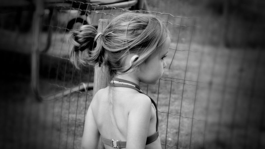 Side view of girl wearing swimwear looking through fence