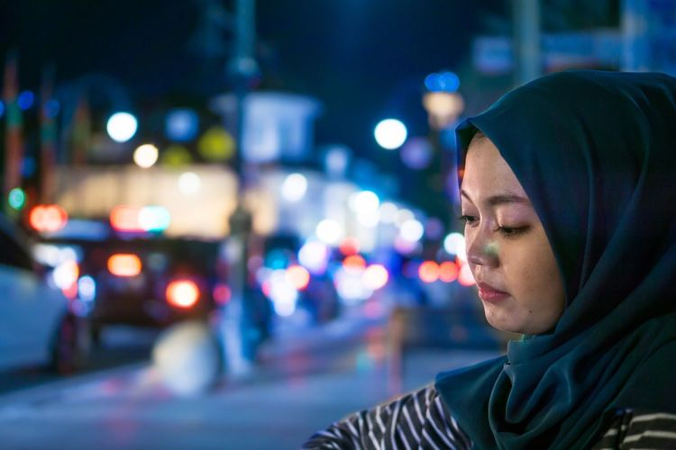 Close-Up Of Young Woman Standing On Illuminated Street At Night