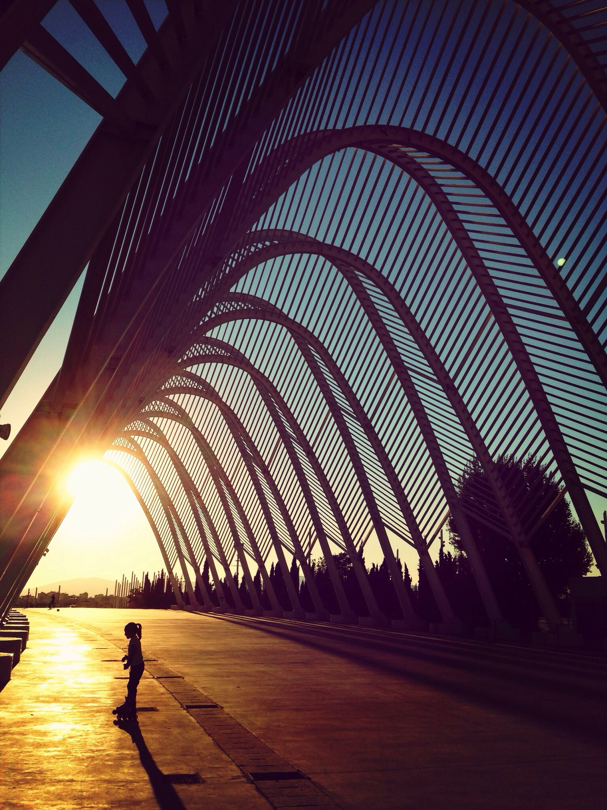 silhouette, sunset, lifestyles, leisure activity, men, walking, sunlight, built structure, person, sky, shadow, sun, illuminated, architecture, full length, railing, city life, standing, sunbeam