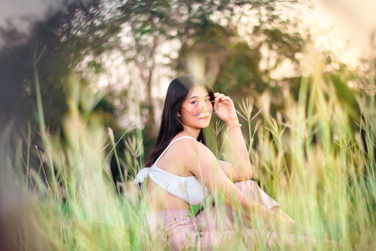Happy young woman sitting on field