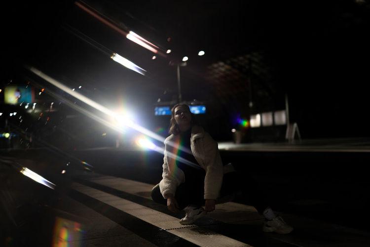 Woman crouching on street against illuminated lights at night