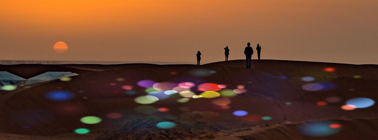 Silhouette people standing on sand by illuminated lights against sky during sunset