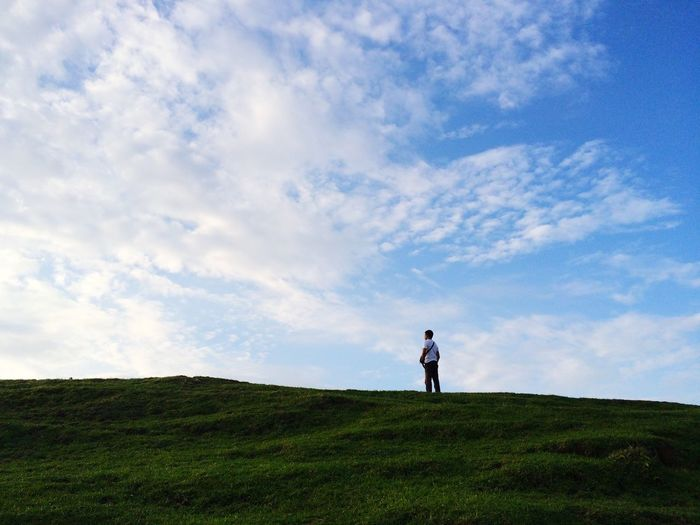 Man standing on field against cloudy sky