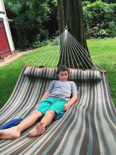 Boy sleeping on hammock in yard