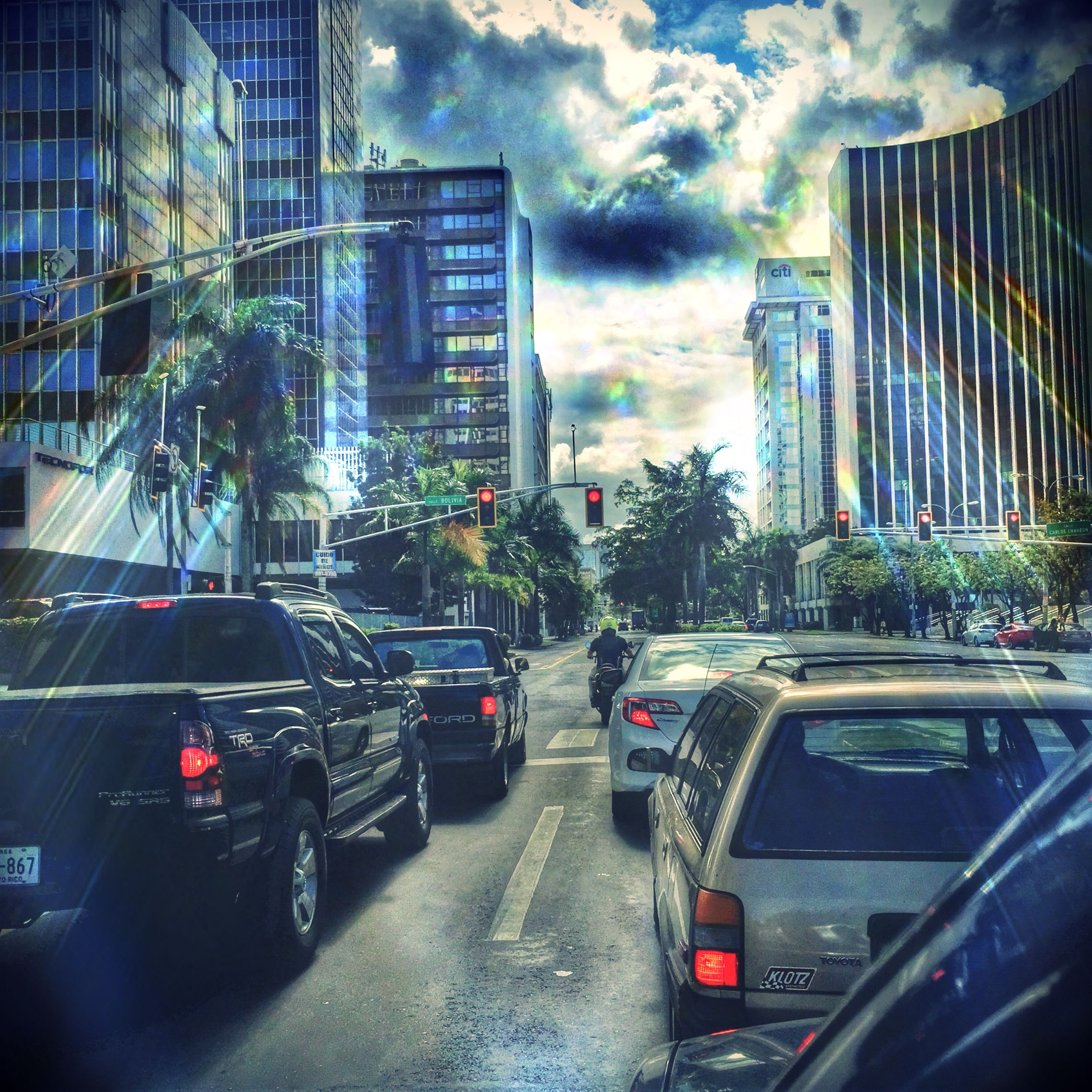 transportation, car, land vehicle, building exterior, city, architecture, mode of transport, built structure, street, road, traffic, sky, city street, city life, skyscraper, office building, road marking, cloud - sky, modern, the way forward