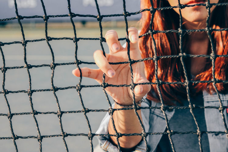Midsection of woman holding chainlink fence in playground