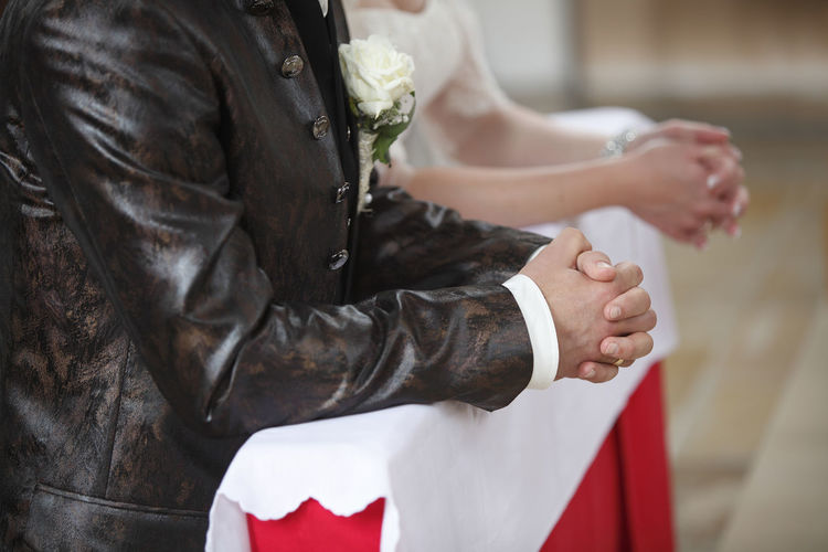 Midsection of bride and groom in church
