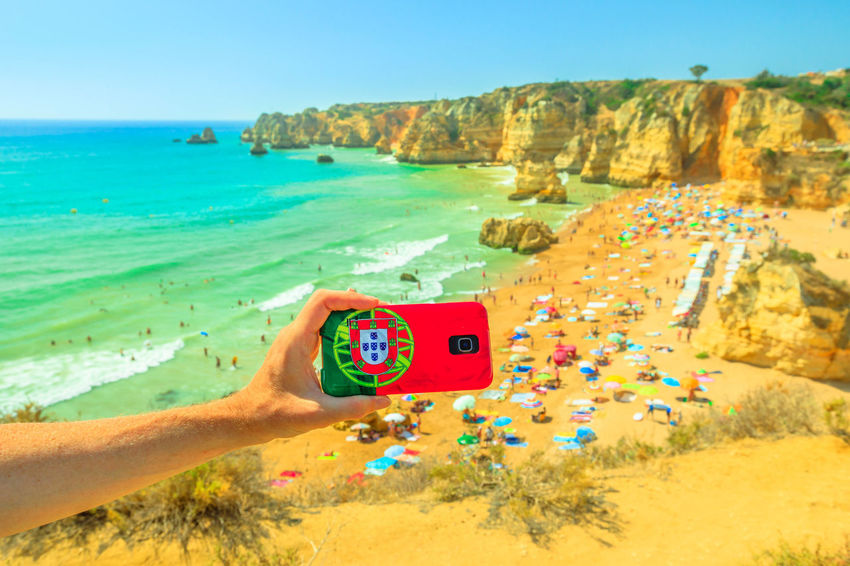 Tourism and travel concept in Algarve. Mobile phone with Portugal flag cover taking photos of Praia do Pinhao in Lagos on Algarve coast, Portugal, Europe. In the distance the famous Dona Ana Beach Lagos Portugal Algarve Portugal Algarve Coastline Algarve Beach Algarve Cliffs And Beach Beach Sea Town Seascape Boat Portrait Pier Aerial View Cliff Jetty Boats Woman Females Girl Selfie Model Camilo Beach Praia Dona Ana Praia Hand Human Hand Human Body Part One Person Holding Land Sky Scenics - Nature Nature Water Day Leisure Activity Photographing Photography Themes Real People Horizon Horizon Over Water Outdoors