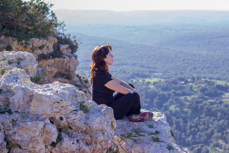 Side view of woman relaxing on rocky cliff