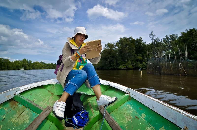 Full length of woman using mobile phone while sitting on rowboat