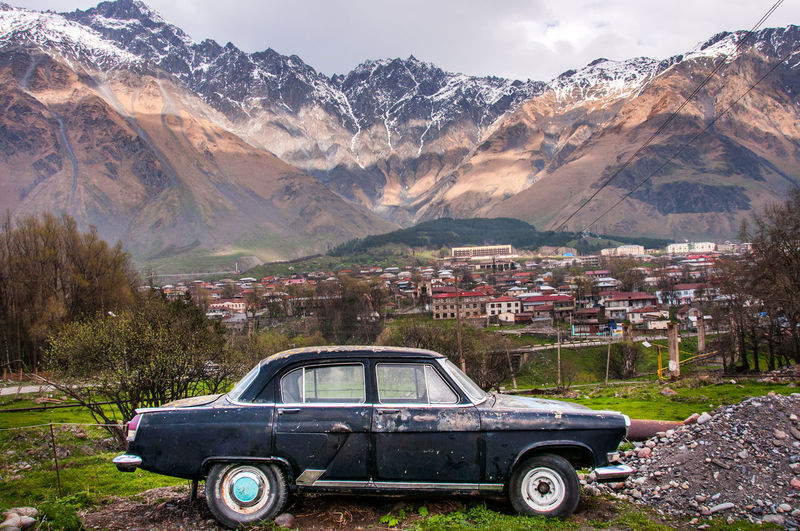 Car Parked On Field Against Mountains In Town