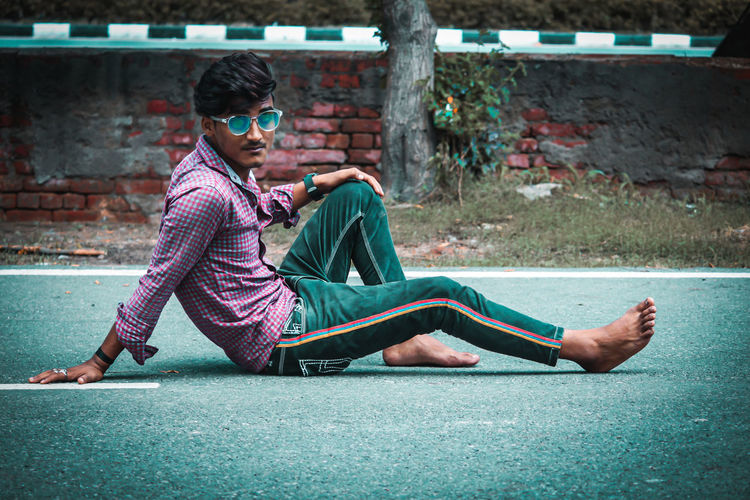 Side view of young man sitting on road in city