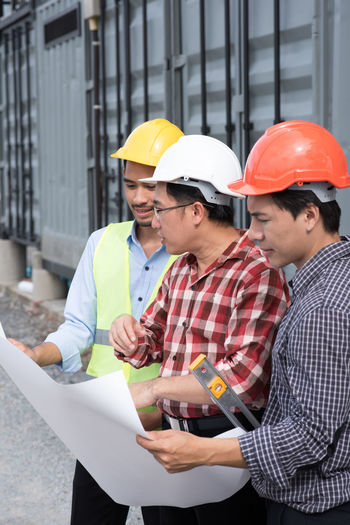 Architecture Building Exterior Built Structure Construction Site Construction Worker Day Discussion Engineer Hardhat  Headwear Helmet Holding Mature Men Men Mid Adult Men Occupation Outdoors Protective Workwear Real People Reflective Clothing Teamwork Togetherness Two People Young Adult Young Men