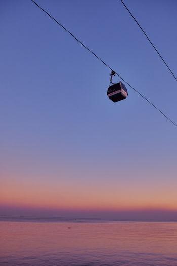 Overhead cable cars over sea against clear sky