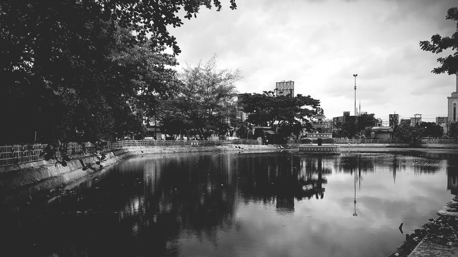 Reflection of buildings and trees in lake against sky