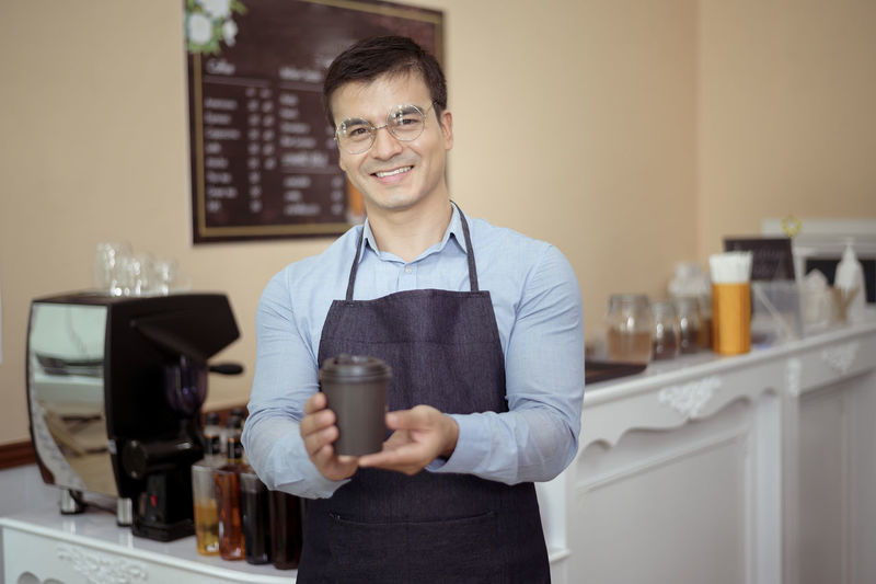 Portrait of a smiling young man holding drink