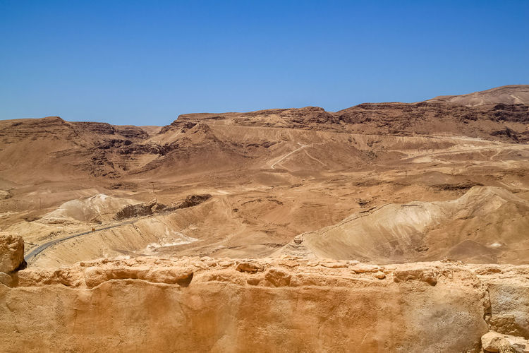 Road travels through the Judean Desert mountains in Israel Israel Southern District, Israel Judean Desert Judea Dead Sea  Jordan Mountains Water Desert Salt Lowest Point On Earth Lowest Point Visit Vacation Tourism Middle East Vacation Destination Masada
