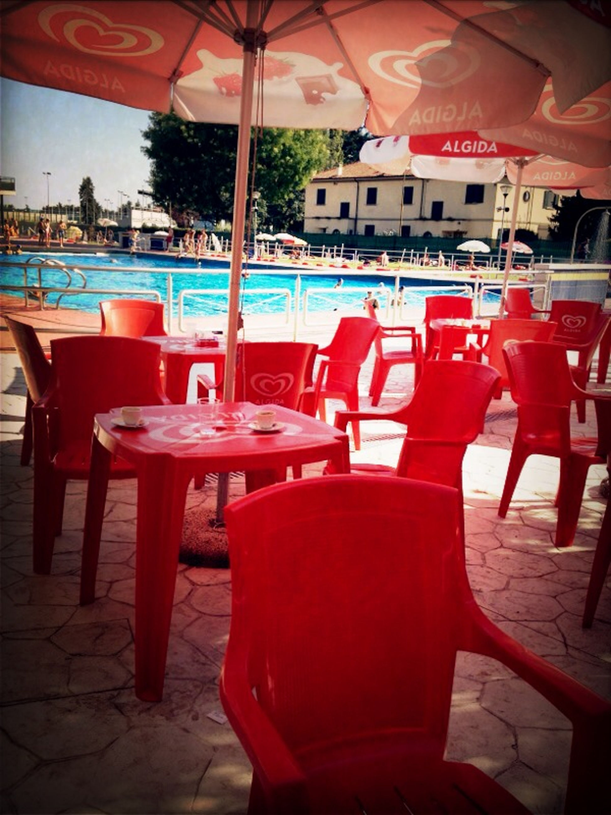 chair, red, empty, restaurant, table, seat, absence, built structure, architecture, sidewalk cafe, cafe, sunlight, incidental people, indoors, water, day, sea, furniture, no people