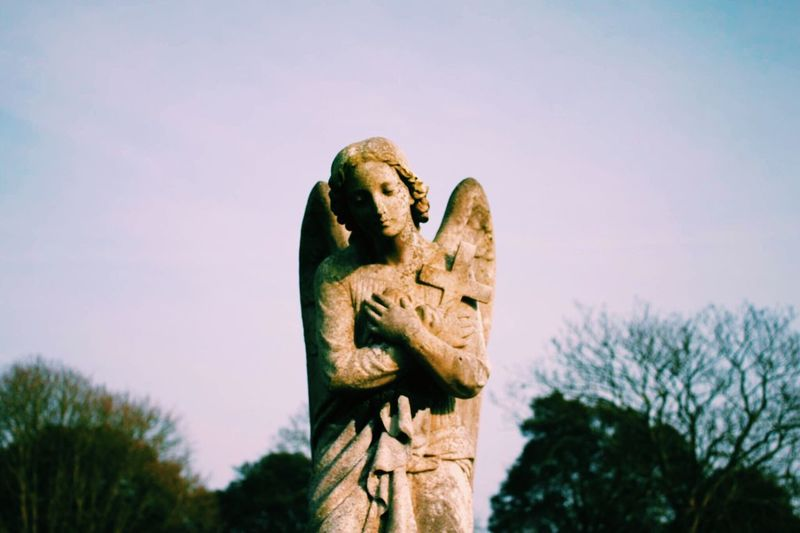 Angel Statue With Cross Against Sky
