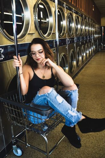 Young woman sitting in basket at laundromat