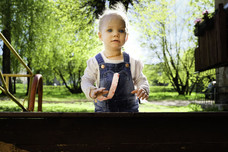 Portrait of cute baby girl standing outdoors