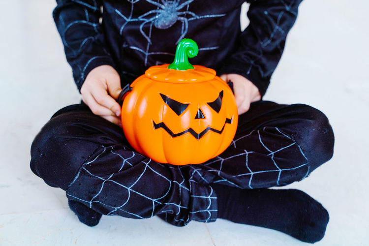 Midsection of man holding pumpkin against orange wall during halloween