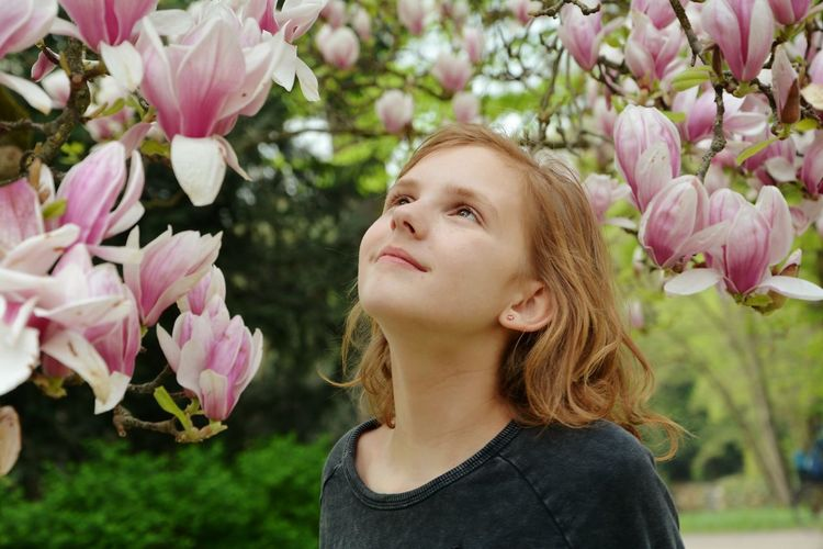 Close-Up Of Girl Looking At Flowers In Park